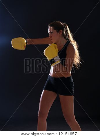 Boxer. Fitness woman wearing yellow boxing gloves