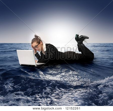 businesswoman with laptop sinking in the sea