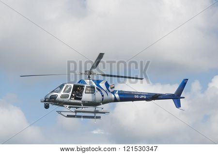 one blue and silver helicopter in the sky and take some picture with the camera