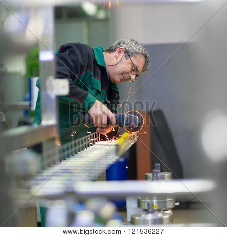 Industrial worker in manufacturing plant grinding steel structure. Sparks from grinding machine in workshop. Industrial background, industry. poster