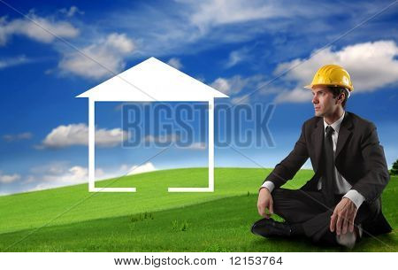 businessman with hard hat planning to build an house