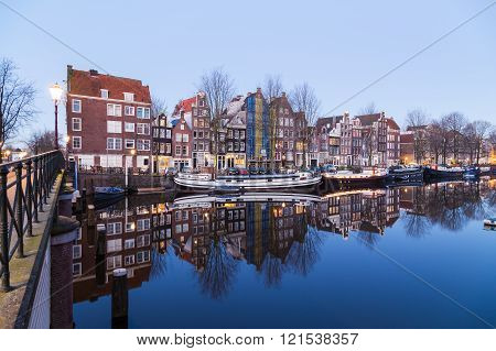 AMSTERDAM NETHERLANDS - 16TH FEBRUARY 2016: A view along the Waalseilandgracht Canal in Amsterdam at twilight. Building boats and reflections can be seen.