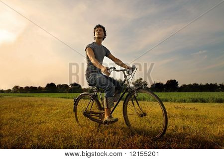 young man riding bicycle in the countryside