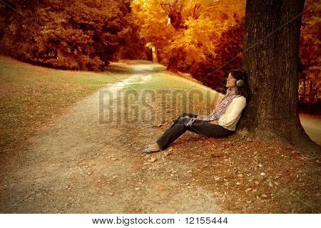 woman sitting against a tree and listening music into autumn landscape
