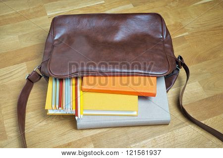 books and pencils in the leather backpack