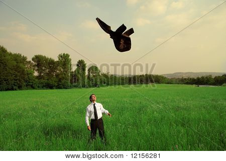 businessman hurling his jacket in a grass field