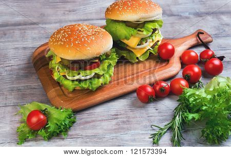 Two big cheeseburger deluxe high on light wooden background in rustic style for gluttons