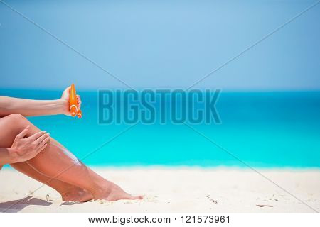 Slim woman applying sunscreen on her legs, sitting on sandy beach with sea background