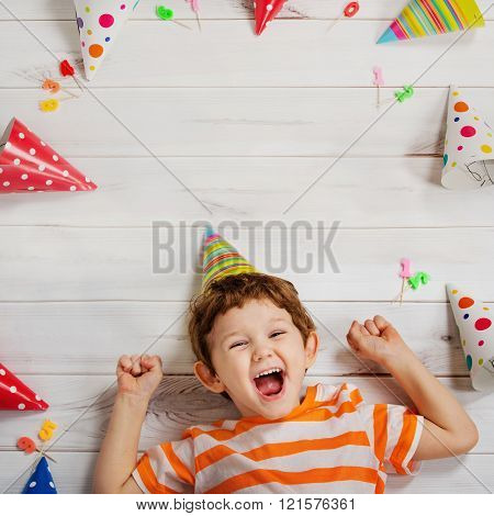 Laughing baby lying on the wooden floor with festive caps and candles on a carnival party. Healthy smiling Happy childhood concept.