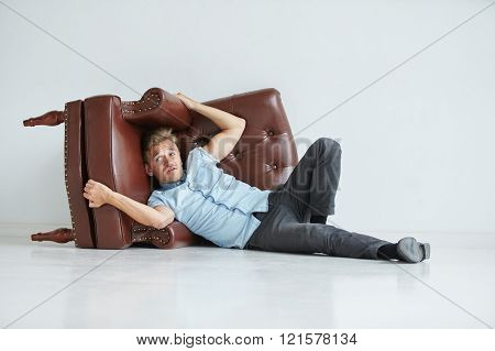 Brutal man in a shirt with short sleeves sitting in the brown chair his fists clenched slightly bent