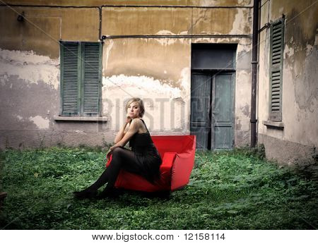beautiful model seated in armchair with old house on the background