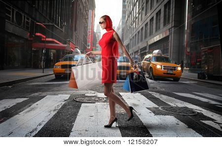 fashionable girl with shopping bags crossing a city street