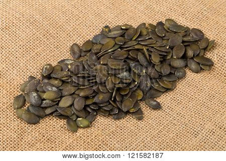 Unshelled pumpkin seeds on burlap