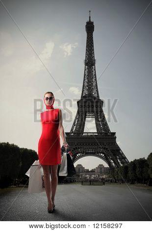 Mujer en vestido rojo llevar algunas bolsas con la Torre Eiffel en el fondo
