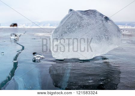 A piece of ice on the surface of the blue frozen Lake Baikal with car at background