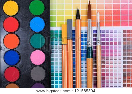 Brushes, watercolor classroom pack and abstract colored palette guide on table.