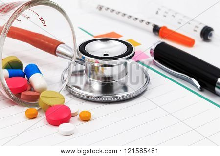 Red stethoscope, syringes, pen, and many colorful pills on blank notepad.