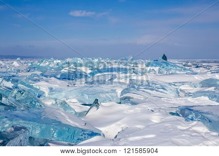 Field of blue transparent hummocks on frozen Lake Baikal. Silhouette of walking woman on blue sky