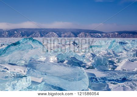 Beautiful Landscape On The Frozen Lake Baikal With Hummocks At Mountains Background. Travel On Baika