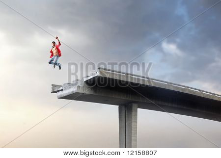 Portrait of a man jumping on a broken highway bridge