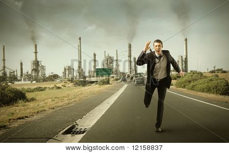Portrait of a businessman running away from a industry plant