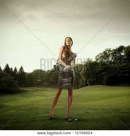 Portrait of a stylish beautiful woman holding a golf club on a green meadow