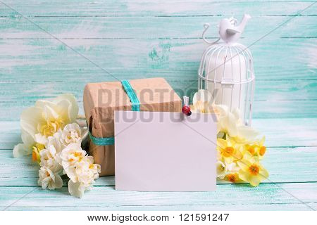 Narcissus Flowers, Empty Tag For Text , Candle, Box With Present  On Turquoise Wooden Planks.