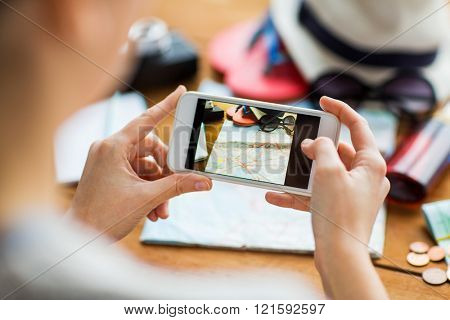 vacation, tourism, travel, technology and people concept - close up of woman with smartphone photographing map and travel stuff