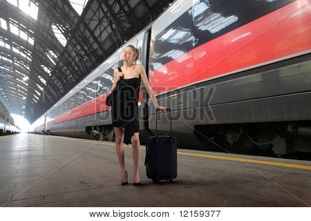 Elegant woman with suitcase standing on the platform of a train station