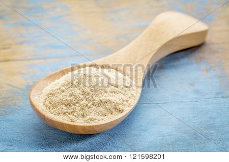 baobab fruit powder on a wooden spoon against blue painted grunge wood
