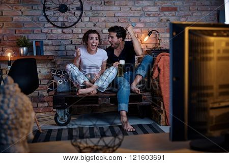 Young couple watching sport on tv, happy for goal.