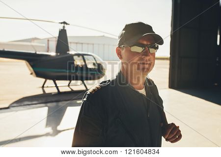 Pilot In Uniform Standing In Airplane Hangar
