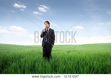 Businessman standing on a green meadow and thinking