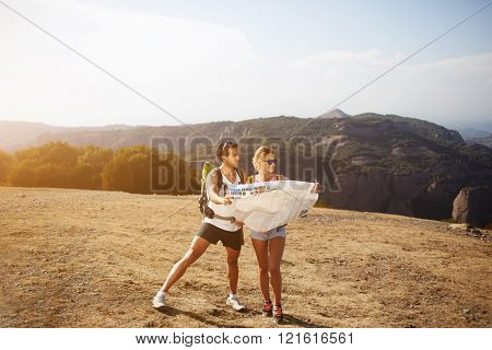 Full length portrait of beautiful couple of a wanderers are exploring map to continue their trek in mountains man and woman hikers are spending time together outdoors during their summer adventure