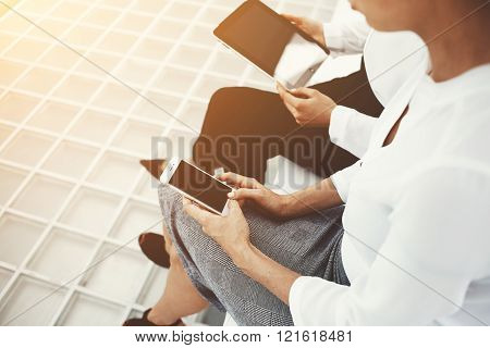 Closeup of a two female are holding mobile phone and touch pad with mock up copy space screens for your advertising text message or promotional content. Women are using cell phone and digital tablet