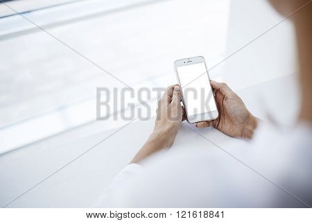 Hipster girl is watching video in web via cell telephone during her recreation time