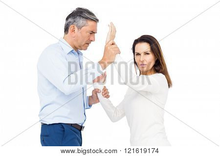 Violent man grabbing wifes wrists against white background