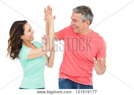 Excited couple giving a high-five on white background