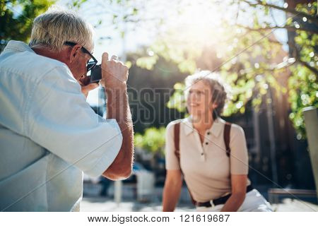 Senior Man Taking Vacation Photographs Of His Wife