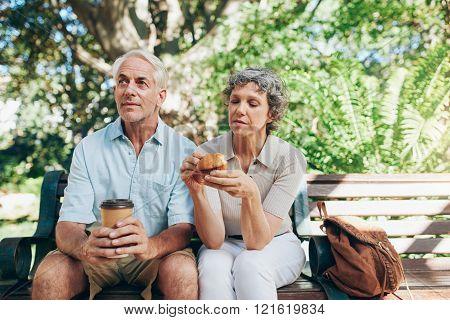 Senior couple sitting outdoors on a park