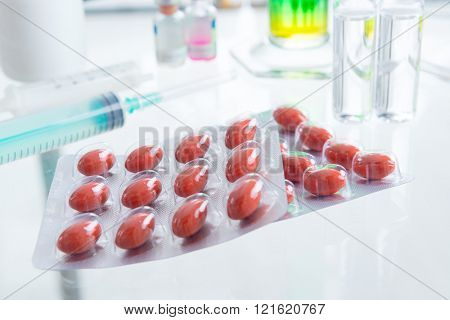 Placebo pills and injection on the table in labolatory