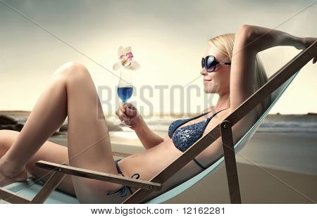 Beautiful woman lying on a deckchair with a cocktail in her hands