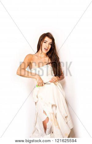 brunette using scissors to cut up her wedding dress