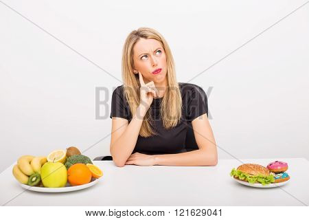 Woman making  decision between healthy and unhealthy foods