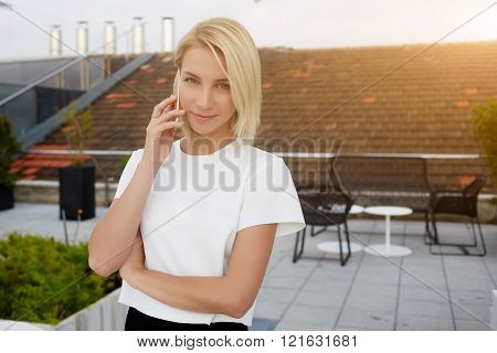 Attractive female is calling via cell telephone during her rest in coffee shop