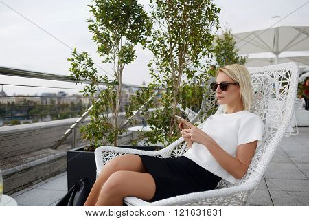 Young beautiful woman is holding mobile phone, while relaxing in cafe outdoors