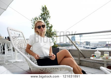 Stylish hipster girl is holding portable touch pad while is sitting in cafe terrace.