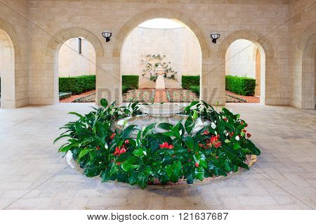 The fountain surrounded by flowers in the temple of Bahai in Acre, Israel.