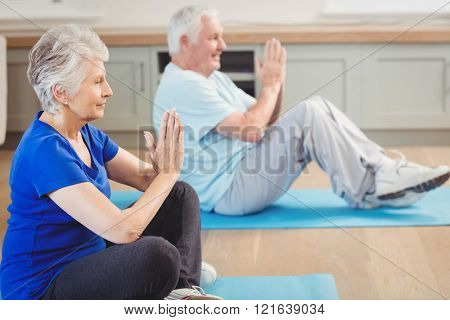 Senior couple performing yoga exercise at home