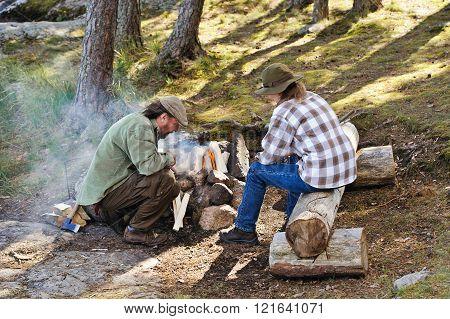 senior couple lighting a camp fire